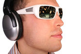 Young man with sunglasses and headphones half-turned — Stock Photo