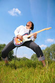 Young man plays on guitar on grass — Stok fotoğraf