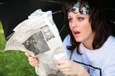 Woman under umbrella with newspaper is surprised — Stock Photo