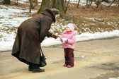 Little girl with snowball speaks with woman — Stock Photo