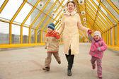 Mother with children on footbridge — Stock Photo