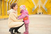 Moeder en dochter kijken elkaar on footbridge based — Stockfoto