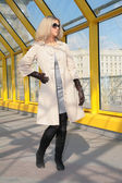 Young blonde in sunglasses and black gloves — Photo