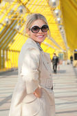 Young blonde in sunglasses smiles — Stock Photo