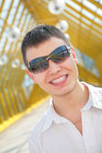 Young smiling man in sunglasses on footbridge — Stock Photo