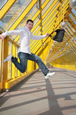 Young man jumps with bag on footbridge — Stock Photo