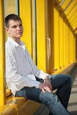 Mladý muž sedí na lávce — Stock fotografie
