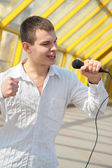 Young man with microphone on footbridge — Stock Photo