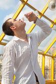 Boy drinks from bottle on footbridge — Photo