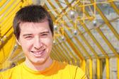 Mladý, usměvavý muž ve žluté košili na lávce — Stock fotografie