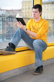 Asian boy sits on footbridge and reads bible — Stock Photo