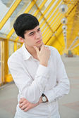 Pensive young man on footbridge — Stock Photo