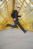 那家伙跳转和 allegorize 的吉他在行人天桥上播放 — 图库照片