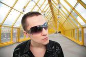 Guy in sunglasses on yellow footbridge — Photo
