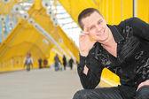 Smiling guy sits on yellow footbridge — Stock Photo