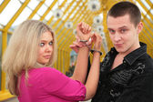 Young man and blonde in handcuff — Stock Photo