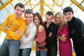 Group of young friends on footbridge look on you — Stock Photo