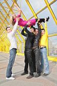 Four boys lift girl up — Stock Photo