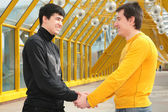 Two friends handshaking on the footbridge — Stok fotoğraf