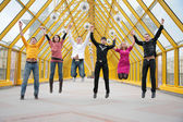 Group of friends jump on footbridge taking as hands — Stock Photo