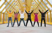 Groep vrienden het staan handen nemen en stijgen ze on footbridge based — Stockfoto