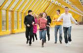 Group of friends runs on footbridge — Stock Photo