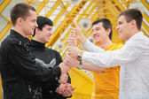 Group of young men make piramid from hands — Stock Photo
