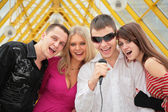 Young sing in microphone on footbridge — Stock Photo
