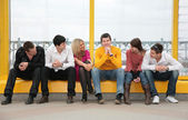 Group of young sit on footbridge — Stock Photo