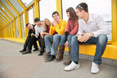 Group of young persons sit on footbridge — Stock Photo