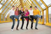 Group of young dance on footbridge — Stock Photo