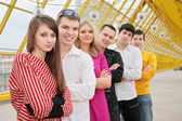 Group of young stand on footbridge — Stock Photo