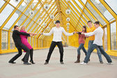 Guy holds belts in the hands, they pull others for them on footbridge — Stock Photo