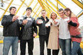 Group of young hold blank cards in hands on footbridge — Stock Photo