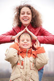 Mother and son show house from hands — Stock Photo