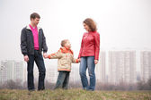 Family stand outdoor in city on spring — Stock Photo