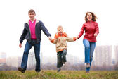 Family jump outdoor in city on spring — Stock fotografie