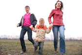 Family run outdoor in city on spring — Stock Photo