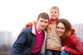 Figlio abbraccia i genitori all'aperto in città — Foto Stock