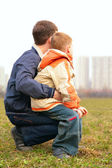 Son on lap of father outdoor in city from back — Stock Photo