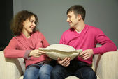 Couple sit on sofa with pillow and look at each other — Stock Photo
