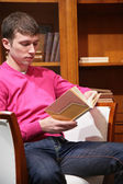 Young man reads book in room — Stock Photo
