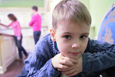 Portrait of pensive boy on kitchen against background of parents — Stock Photo