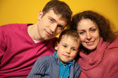 Family on yellow background — Stock Photo