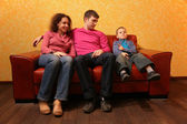 Family seating on red leather sofa — Stock Photo
