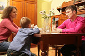 Family seats behind table — Stock Photo