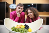 Young couple on kitchen and vase with fruits — Stock Photo