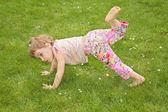 Niña hace gimnasia ejercicio sobre hierba — Foto de Stock