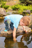 Boy has lowered hand in stream — Stock Photo