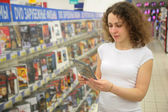 Young woman in shop holds in hands dvd — Stock Photo
